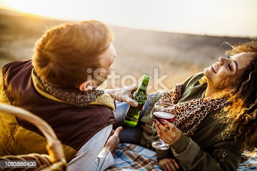 Cheerful couple laughing while drinking alcohol on a picnic in autumn day.