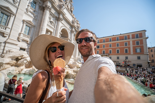 Cheerful couple enjoying Italian vacations in Rome eating gelato ice cream at the Piazza di Trevi fountain