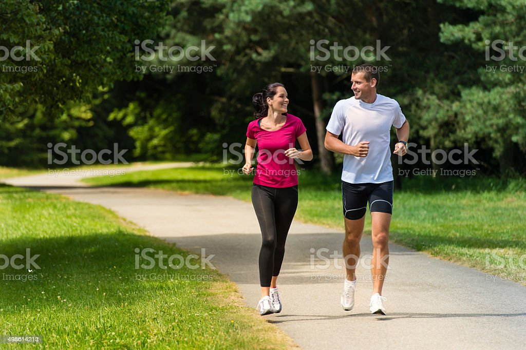 Cheerful couple friends running in park stock photo