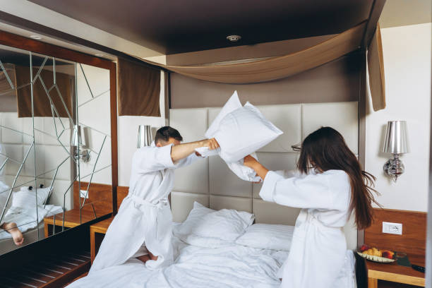 Cheerful couple have fun in the bedroom fighting with big pillows at home stock photo