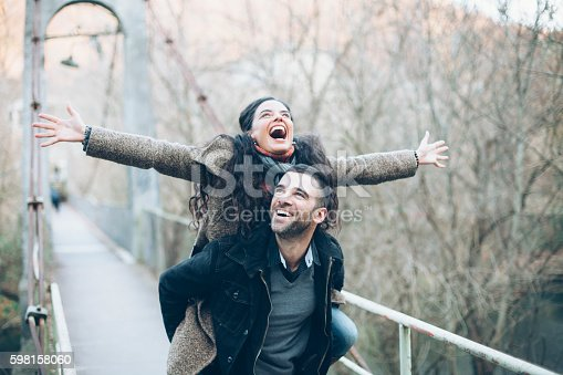 Young couple having fun in piggyback ride on a bridge. Woman laughing with arms outstretched, looking up. Both wears warm clothes. Trees on background.