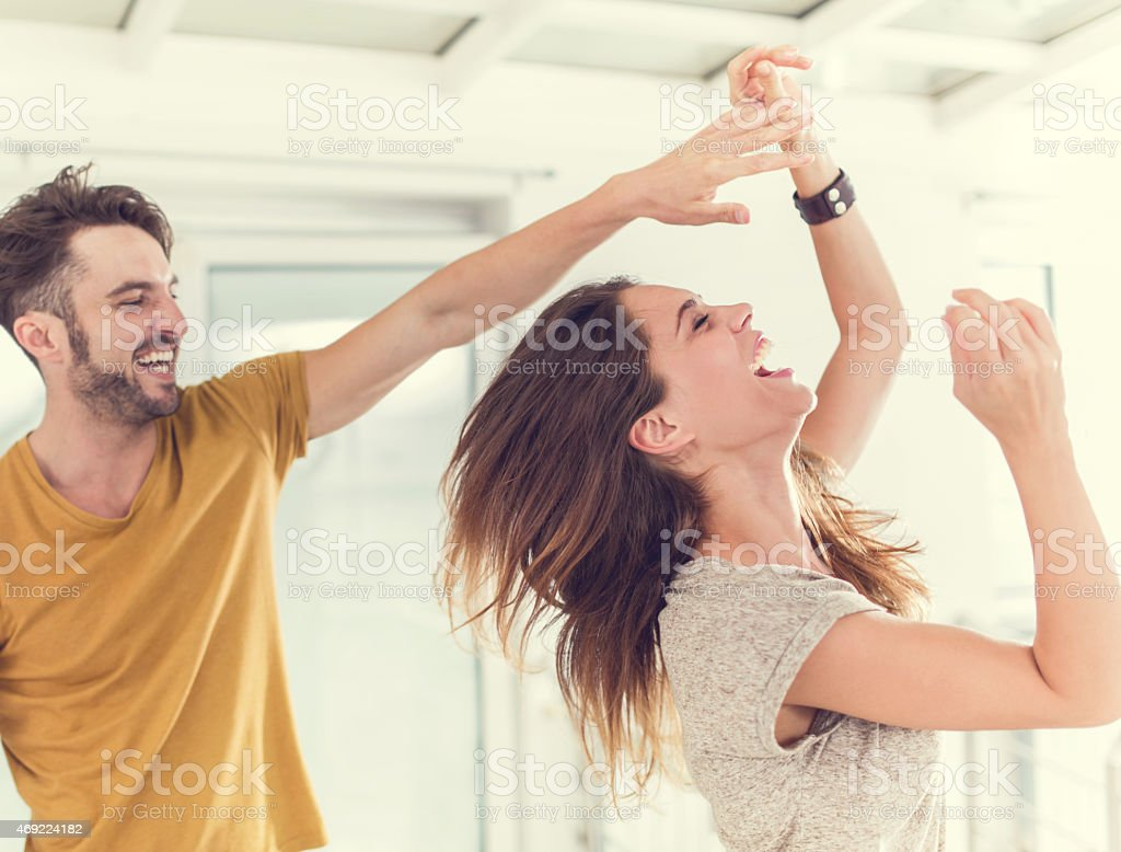 Cheerful couple having fun while dancing together. stock photo