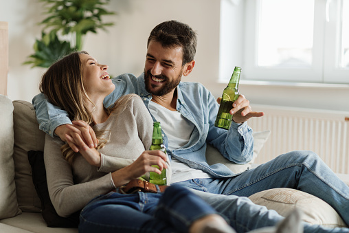 Young happy couple communicating while sitting on the sofa and drinking beer