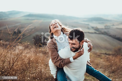 Young cheerful couple having fun while piggybacking on a hill.