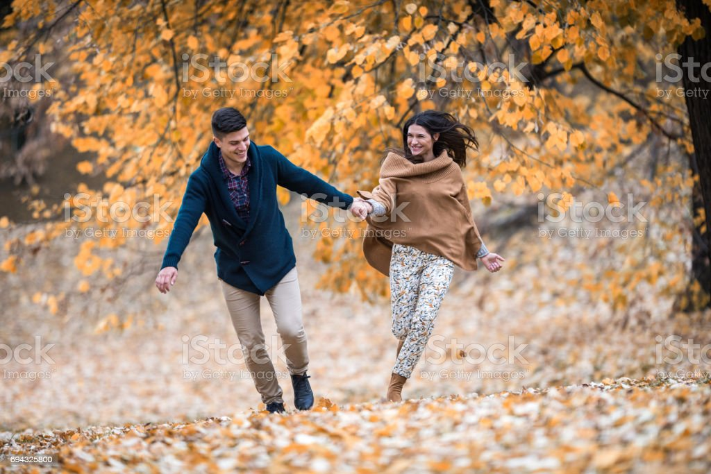 Cheerful couple having fun while running in the park. stock photo