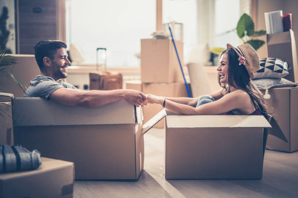 cheerful couple having fun while sitting in cardboard boxes at their new home. - relocation stock photos and pictures