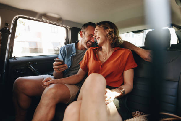 Cheerful couple in rear seat of car stock photo