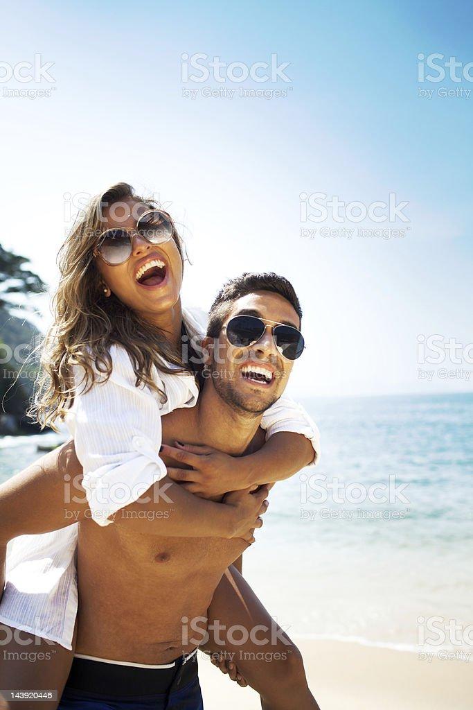 Cheerful couple, man piggyback a beautiful woman on the beach. stock photo