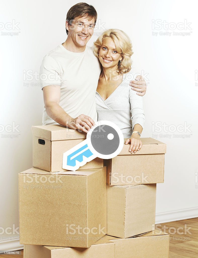 Cheerful couple moving into new home and holding key sign. royalty-free stock photo