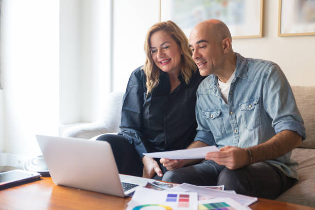 Cheerful couple of clients consulting interior designer stock photo