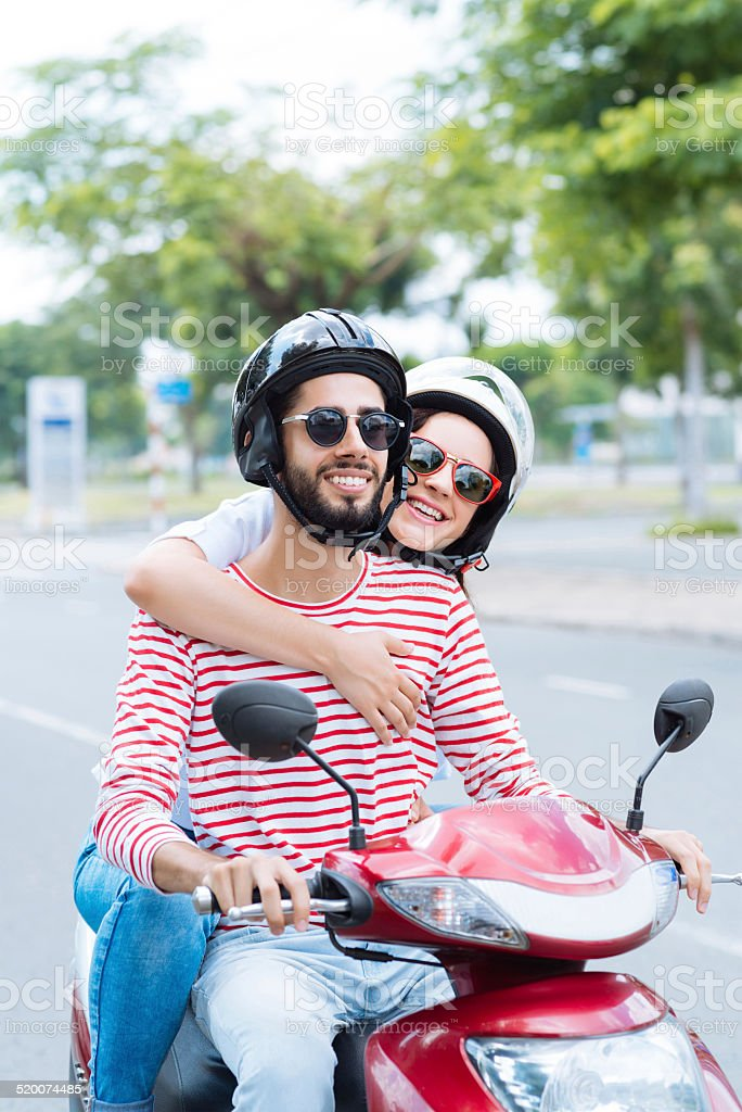 Cheerful couple on scooter stock photo