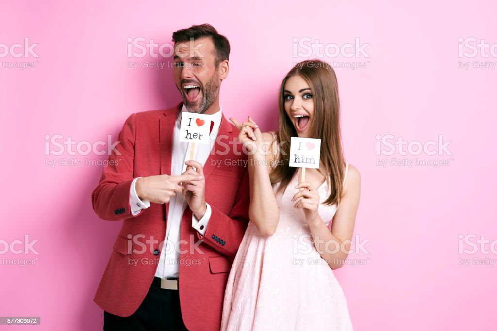 Cheerful couple pointing at each other stock photo