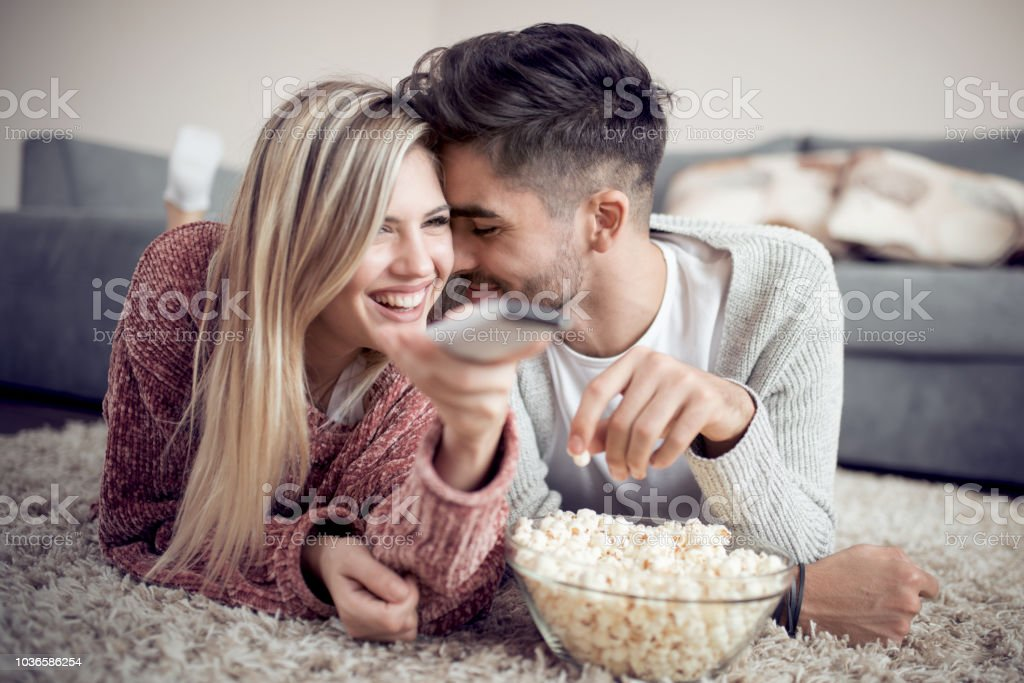 Cheerful couple relaxing at home stock photo