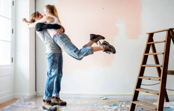 Cheerful couple renovating the house stock photo
