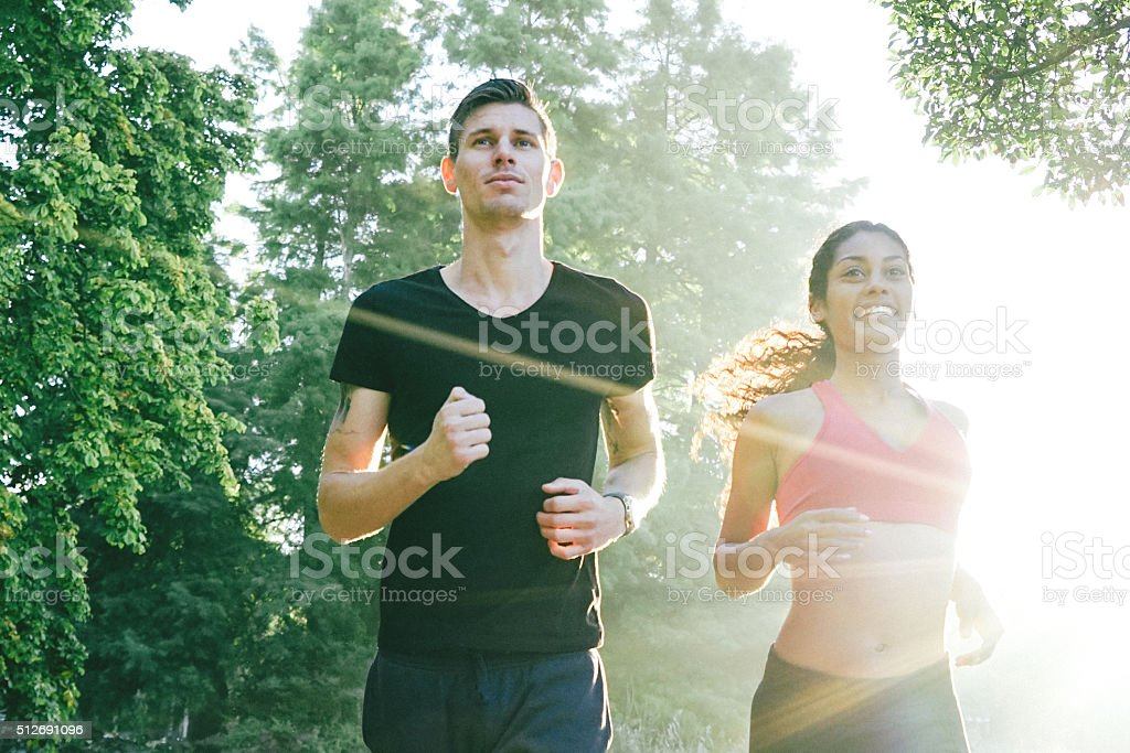 Cheerful Couple Running Outdoors In The Early Morning stock photo