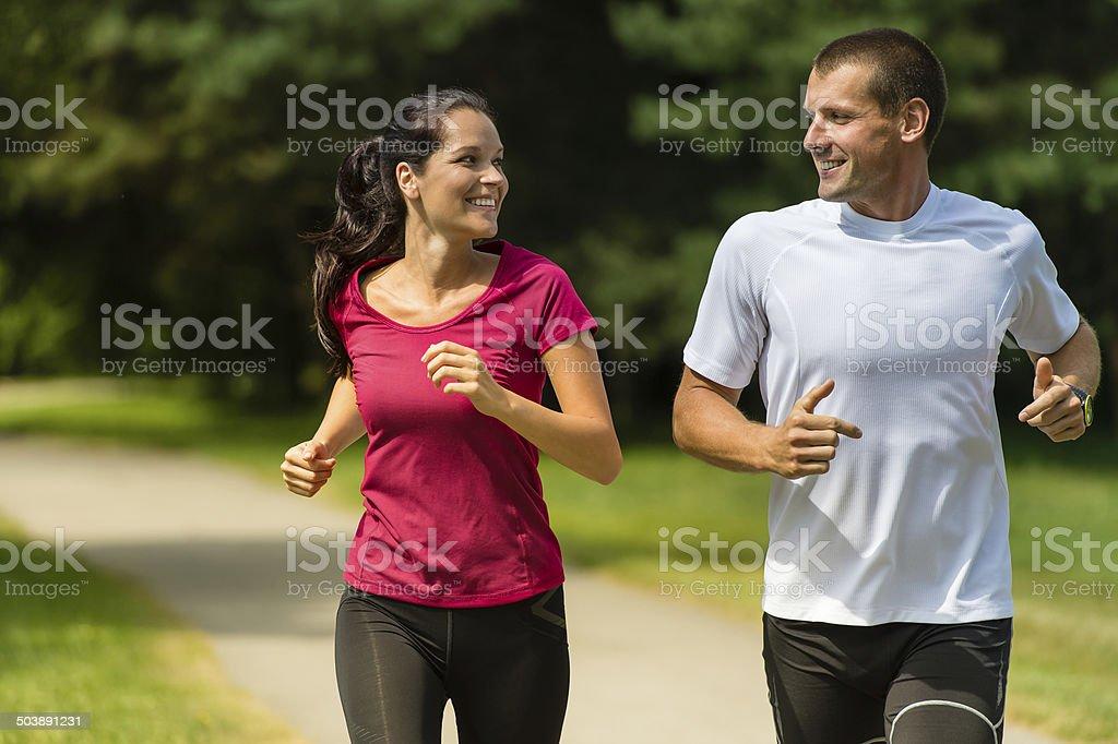 Cheerful couple running outdoors stock photo