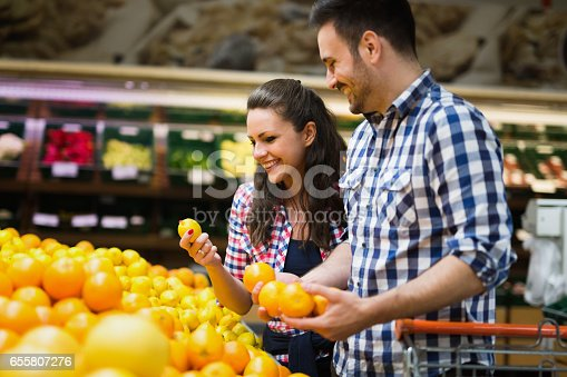 istock Cheerful couple shopping for organic fruit in supermarket 655807276