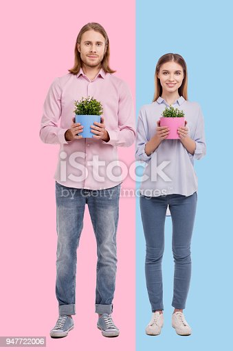istock Cheerful couple showing matching flower pots 947722006