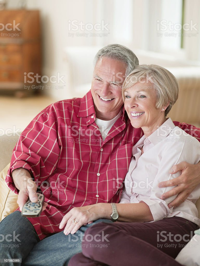 Cheerful couple sitting together on couch with remote control in hand royalty-free stock photo