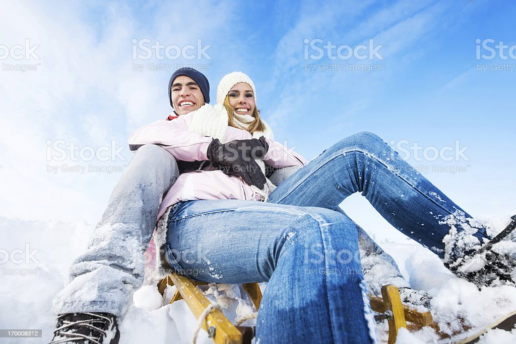 Cheerful couple sledging against the sky royalty-free stock photo