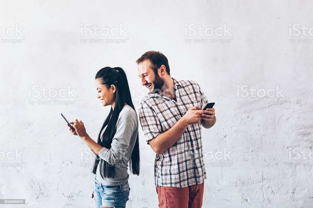Cheerful couple standing back to back and having fun stock photo