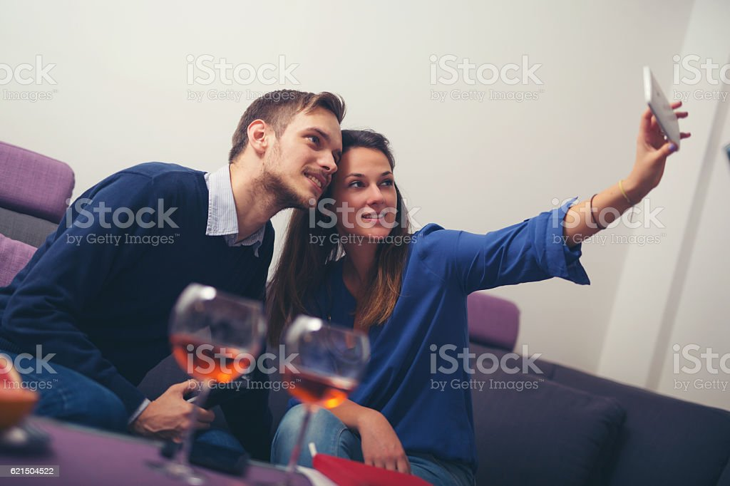 Cheerful couple taking a selfie with a smartphone at home foto stock royalty-free