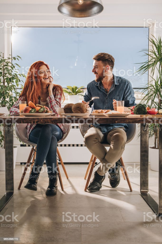 Cheerful couple talking while having a meal at dining table. royalty-free stock photo