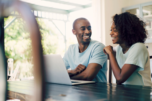 A photo of happy couple using laptop at home. Cheerful man sitting with woman at table. Both are in casuals.