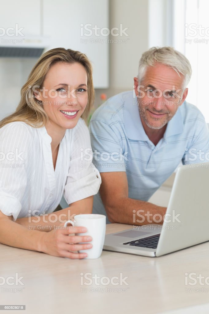 Cheerful couple using laptop together at the counter stock photo