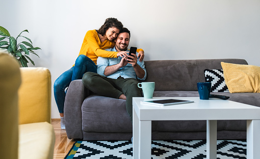 Man holding in hands phone and woman showing screen and smiling together embraced while sitting on sofa at home