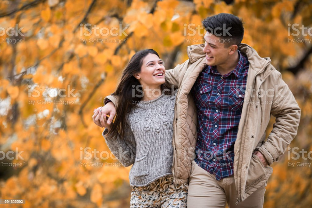 Cheerful couple walking embraced in autumn day and communicating. stock photo