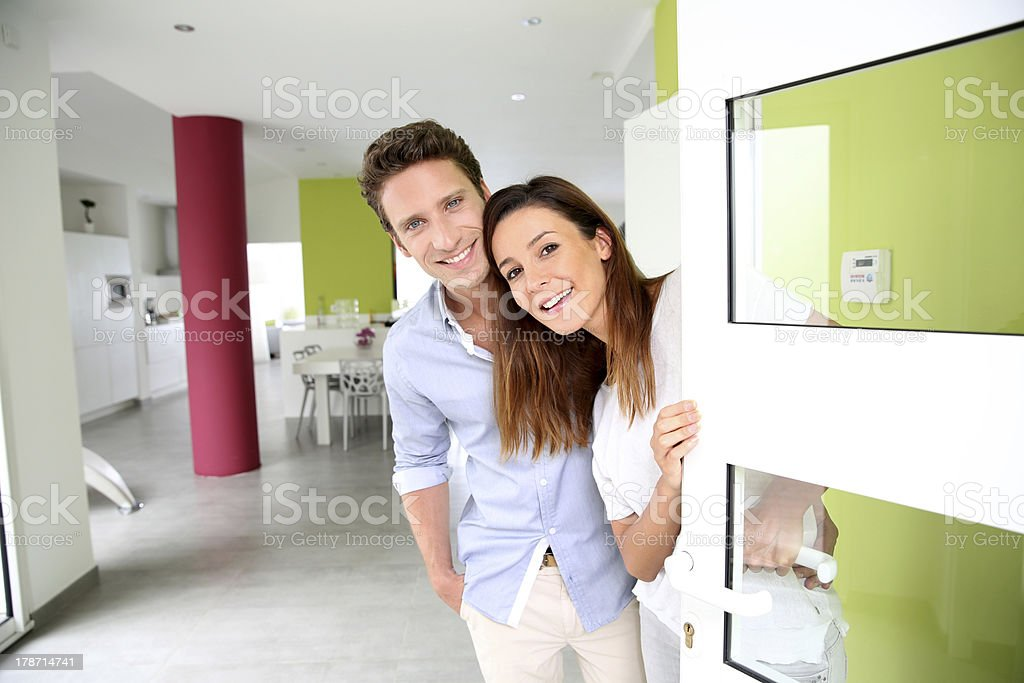 Cheerful couple welcoming people at entrance door stock photo