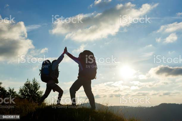 Photo of A cheerful couple with backpacks on top of the mountain give each other a high five against the background of the mountains and the cloudy sky with a bright sun at sunset. Bottom view