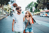 Charming Australian couple going shopping. Adult couple choosing Christmas or St. Valentines  buying nice presents. Woman with shopping bags in summer time on streets of big city.