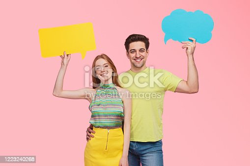 Happy young man and woman with blank speech and thought bubbles smiling and looking at camera while representing human communication against pink background