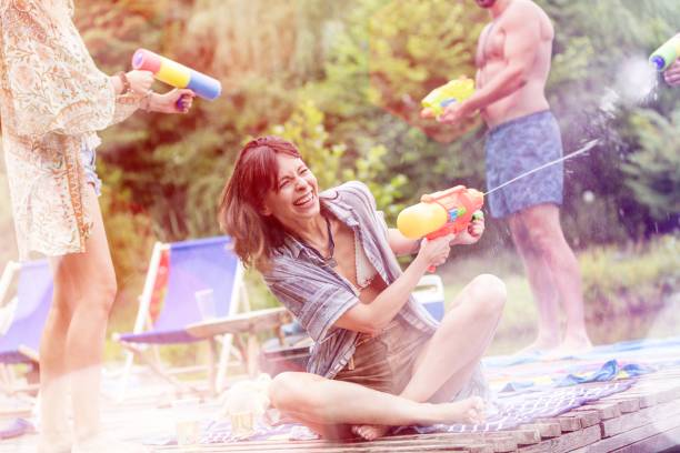 Cheerful couples enjoying with squirt guns on pier during summer stock photo
