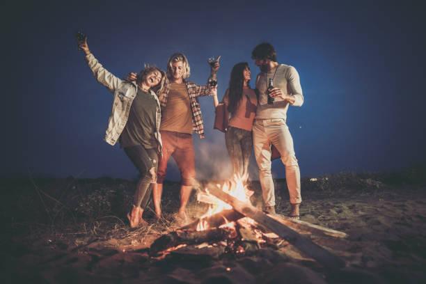 fröhliche paare, die sich am lagerfeuer vergnügen. - tanz camp stock-fotos und bilder