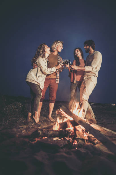 cheerful couples toasting with alcohol by the campfire at night. - falò spiaggia foto e immagini stock