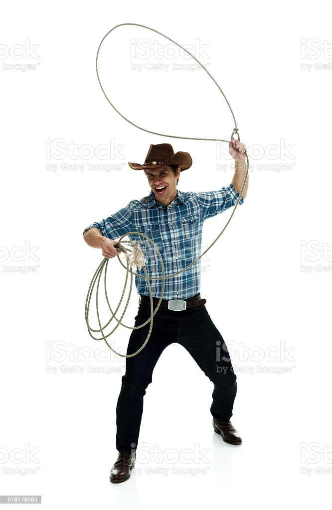 Cheerful cowboy lassoing stock photo