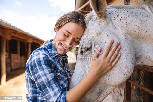 Beautiful cowgirl in plaid shirt enjoying her time spent with her horse at the stable.