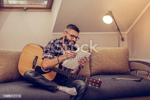 istock Cheerful creative bearded man reading note charts 1098012110
