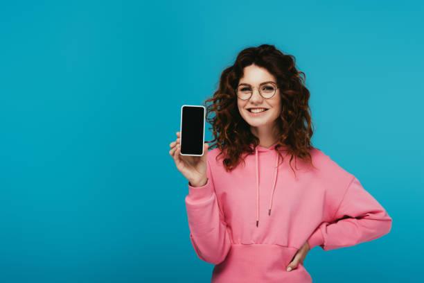 メガネで陽気なカーリーの女の子が腰の上に手で立って、青に空白の画面でスマートフォンを保持 - 見せる ストックフォトと画像