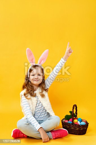Cheerful cute beautiful child sitting on the floor with a basket of Easter eggs on a yellow background in the studio. Happy little girl in bunny ears shows index finger up on copy space.