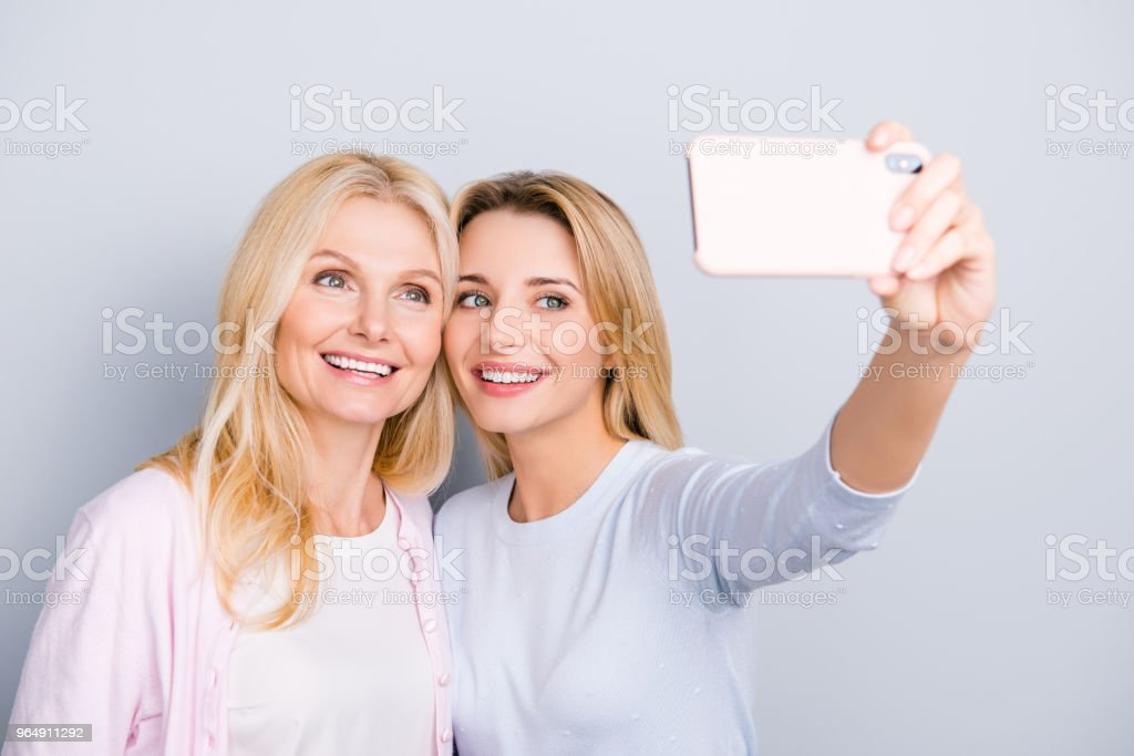 Cheerful cute charming blogger shooting self portrait on front camera with attractive pretty mom using smart phone enjoying time together, selfie mania, addicted people, isolated on grey background royalty-free stock photo
