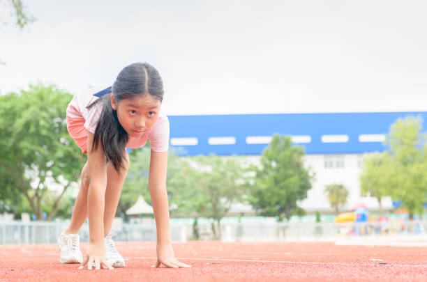 Cheerful cute girl in ready position to run on track, stock photo