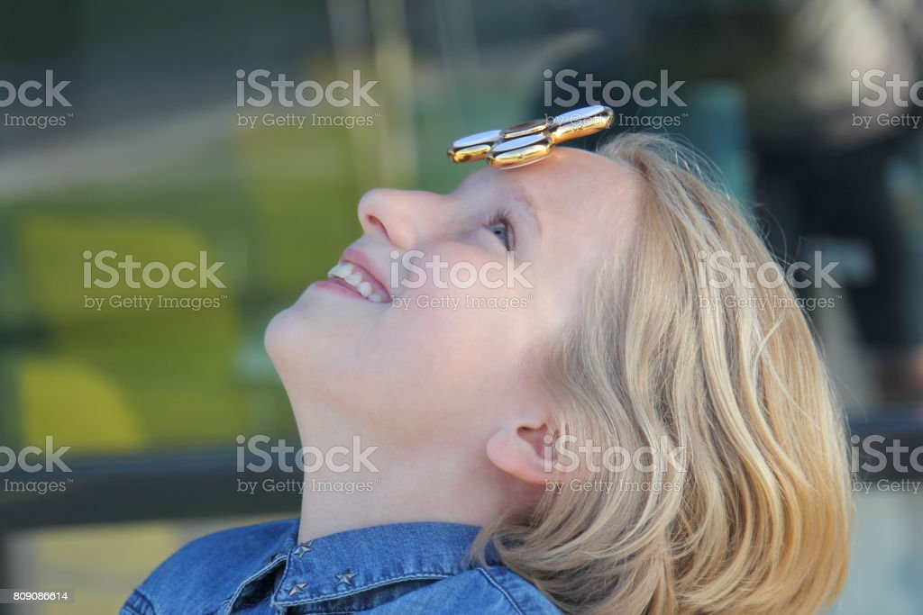Cheerful cute school aged girl playing with a gold fidget spinner. A popular trendy toy spins on the forehead. stock photo