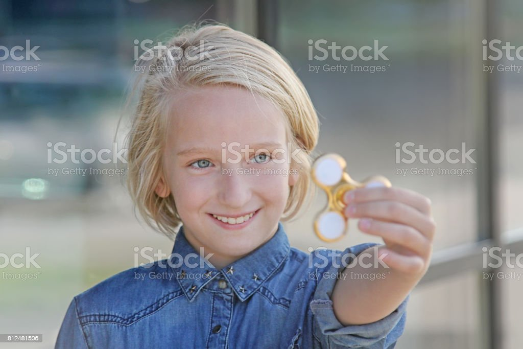 Cheerful cute school aged girl playing with a gold fidget spinner. A popular trendy toy. stock photo