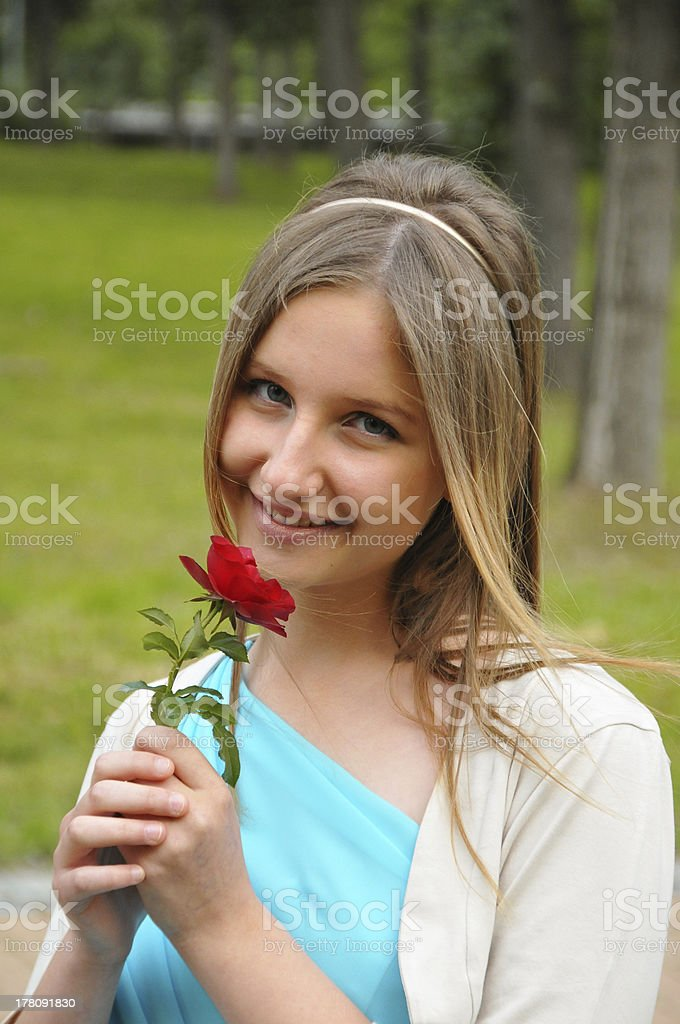 Cheerful cute teenage girl with blue eyes holding red rose royalty-free  stock photo