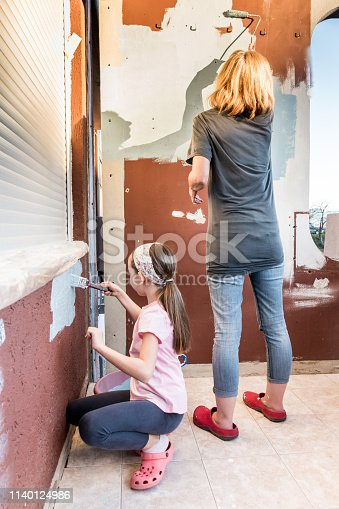 Cheerful Daughter and Mother Painting Balcony Wall Together