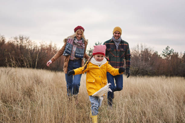 Cheerful daughter running through meadow during hike with her parents on a Christmas morning stock photo